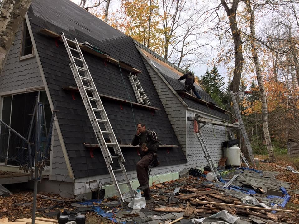 photo of two men repairing the roof of an aframe house