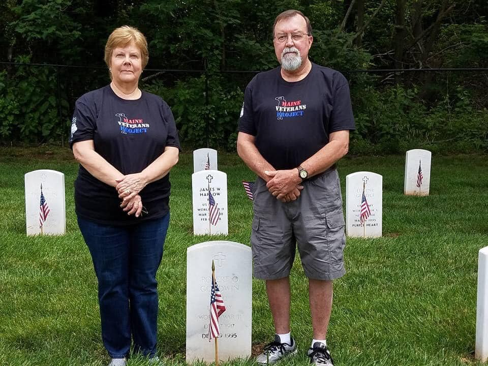 photo of man and woman wearing maine veterans project shirts next to grave in cemetery