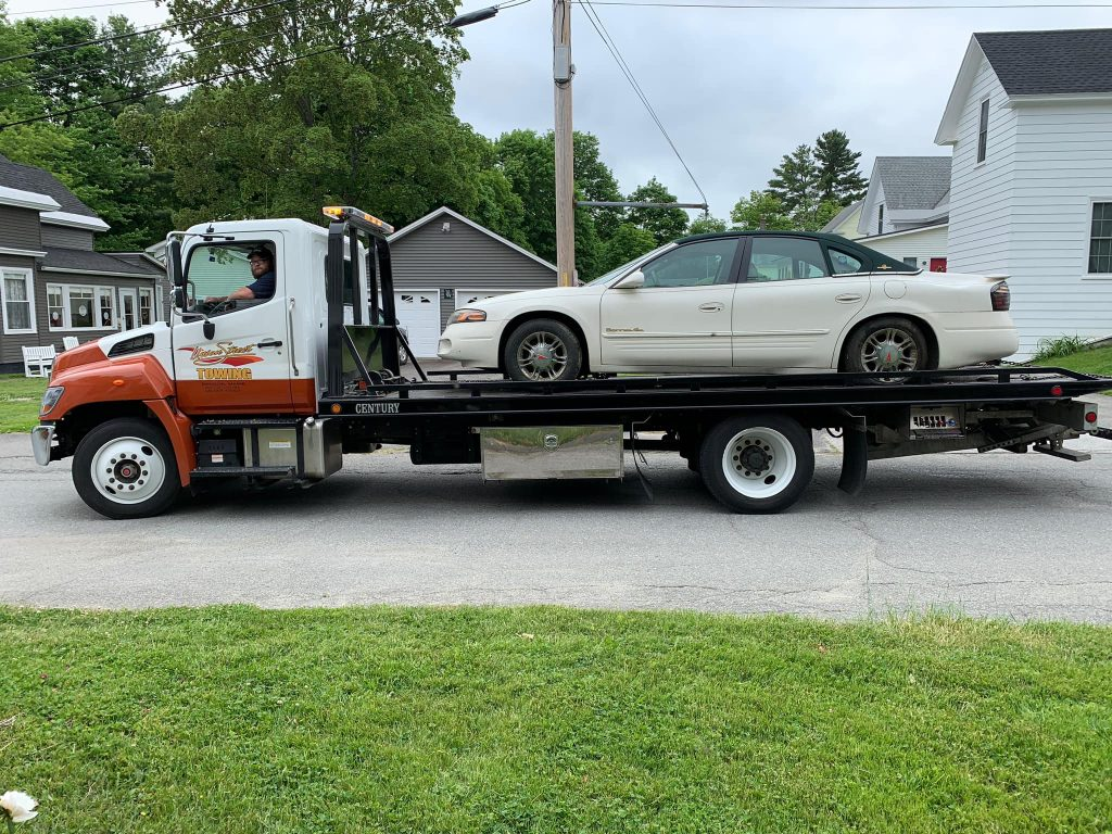 photo of man driving a flatbed towing truck with a white car on the back
