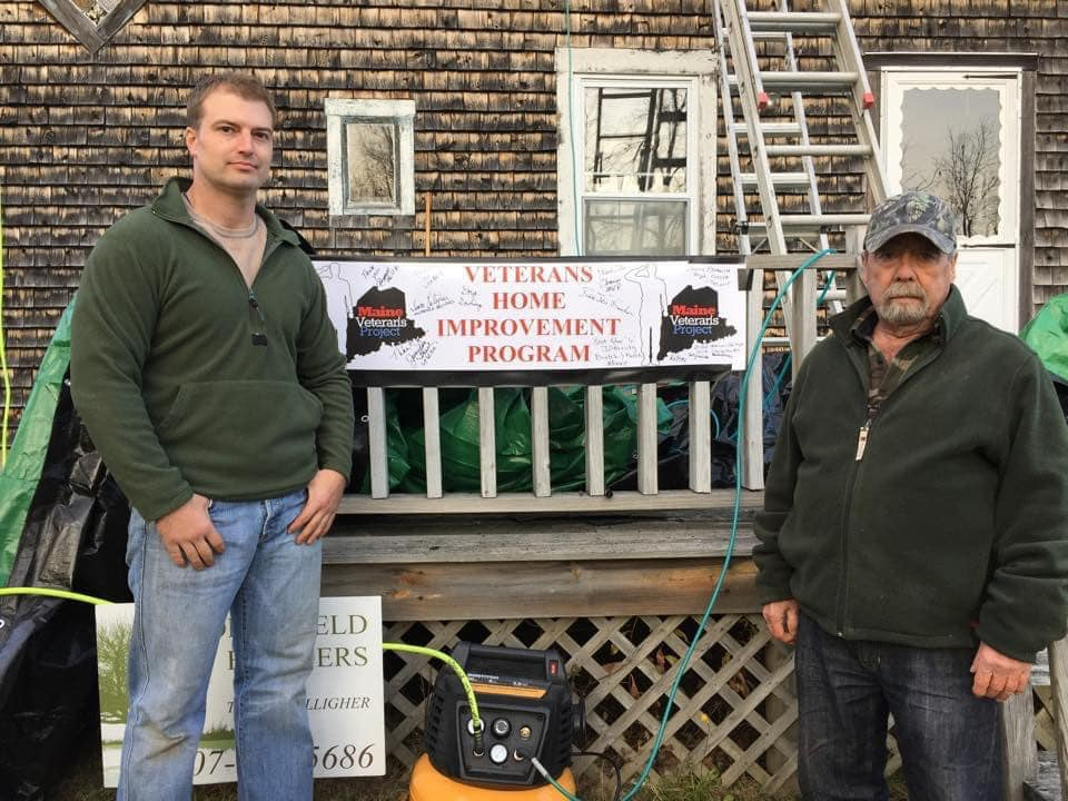 photo of two men standing in front of a house with a veterans home improvement program banner