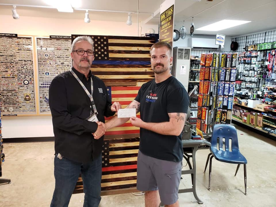 photo of men shaking hands in store while one hands the other with a check