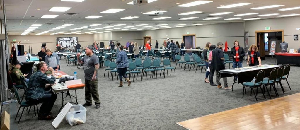 photo of a conference room filled with tables, chairs and people milling about