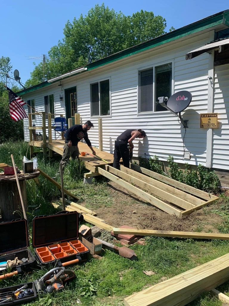 photo of two men building a ramp outside of a home