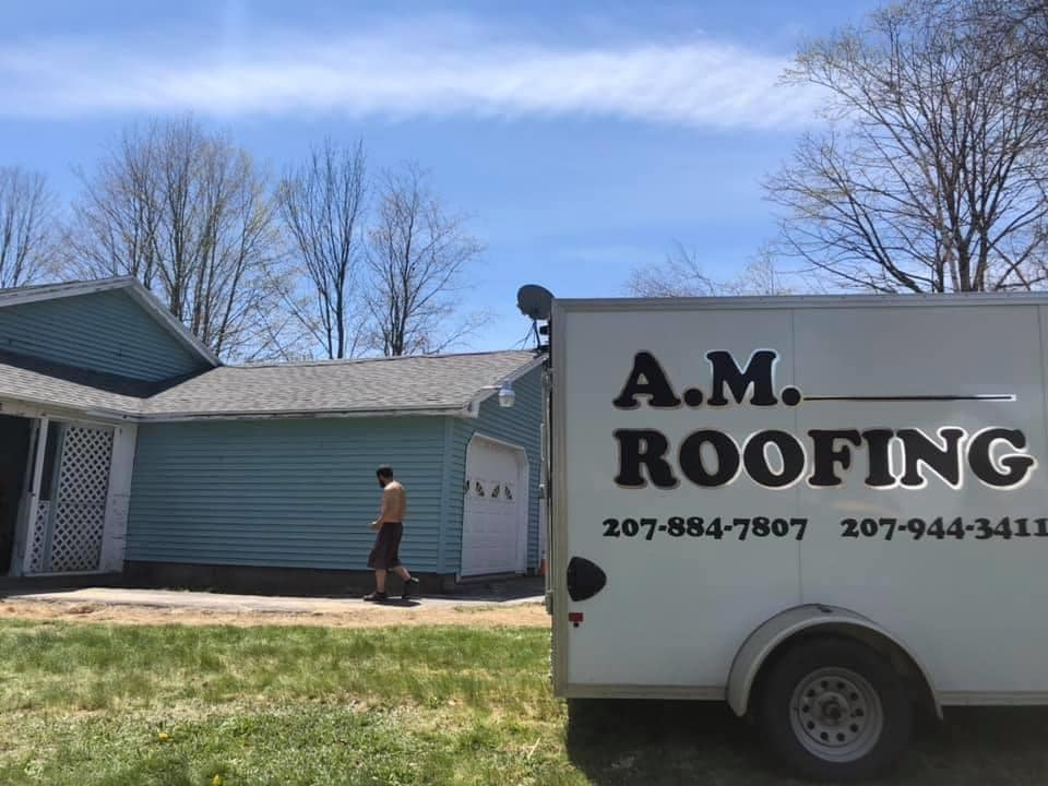 photo of man walking along garage with a.m. roofing truck in front