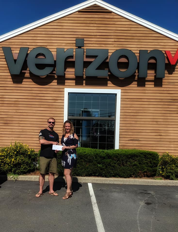 photo of man and woman shaking hands in front of verizon store holding a check