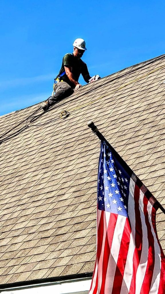 photo of man working on roof with hard hat and american flag